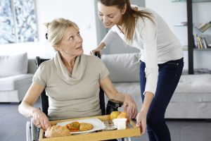 Young woman helping senior woman at home